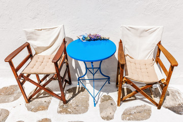 Welcoming chairs and blue table outside a bar in Mykonos