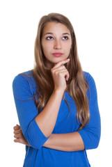 Blonde Frau mit blauem Shirt denkt nach