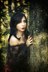 girl vampire in retro dress, in a black cloak, in the forest