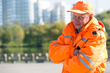 Positive caucasian man worker at city buildings background