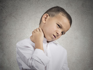 portrait boy with neck pain isolated on grey wall background