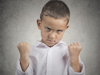 angry child, boy with fist up in air, pissed off grey background