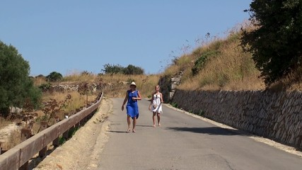 Two girls on a rural road down the hill. Sicily