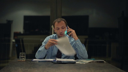 Angry businessman with documents talking on cellphone in home at