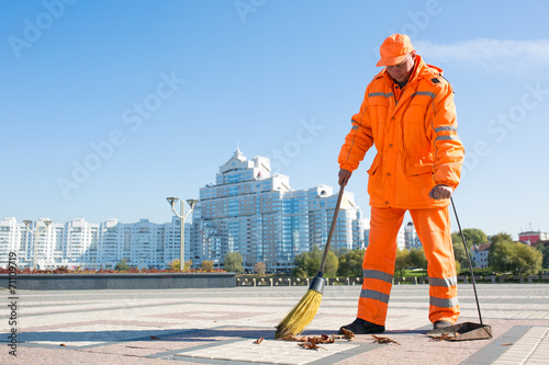 Man road sweeper caretaker cleaning city street with broom tool - 71109719