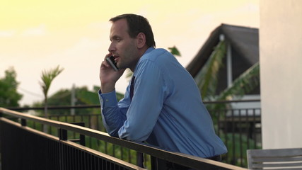 Businessman talking on cellphone on the terrace in the evening