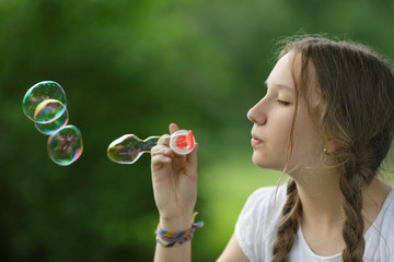 teenage girl blows soap babbles in the park