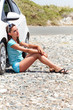 Young woman is sitting on the road near the car