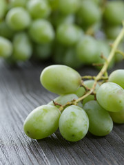 ripe green grapes on black wood table