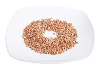 plate with buckwheat groats isolated on white background