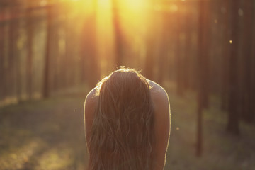 girl with long hair closing face in moody forest