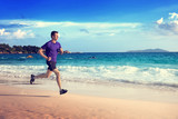 Fototapeta Man running on tropical beach at sunset