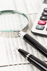 Pen, calculator, and magnifier rest on stock price detail financ