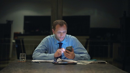 Businessman texting, sending sms on smartphone in the office at