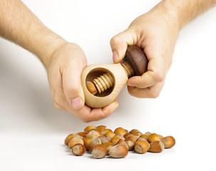 Male hands cracking hazelnuts