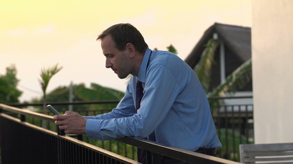 Businessman texting, sending sms on smartphone on the terrace in