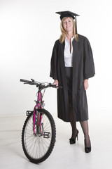 Mature Uni student standing in cap gown holding bicycle