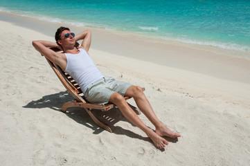 Man in chair sunbathing on the beach near the sea