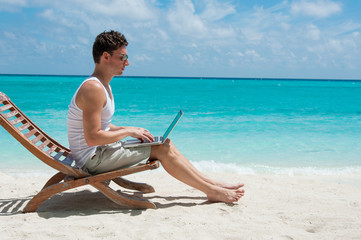 Man sitting with laptop on the beach