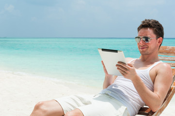 Man sitting with tablet on beach