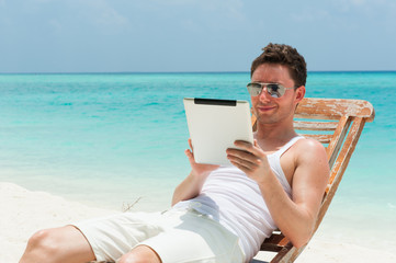 Man sitting with tablet on the beach with the sea, ocean view