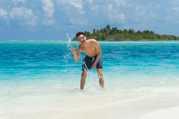 Man splash water of the ocean at the background of island
