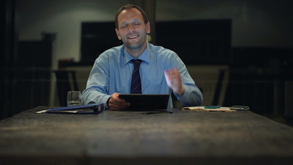 Portrait of smiling businessman with tablet computer at home dur