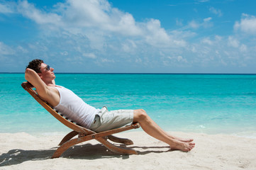 Man sunbathing on the beach near the ocean