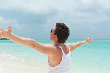 Man walking on the beach with open arms enjoying the weather