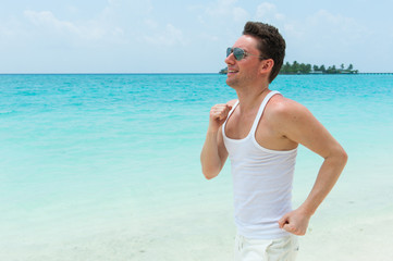Smiling man running on the beach, Maldives island