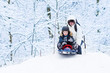 Little boy sledding down a hill with his father helping him
