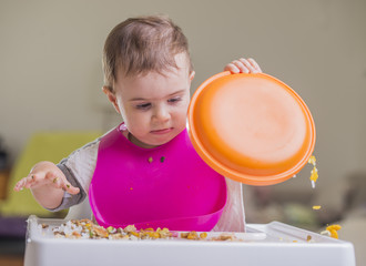 cute baby girl playing with plate during meal time