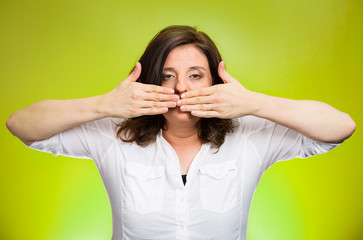 woman covering mouth on green background. Speak no evil concept