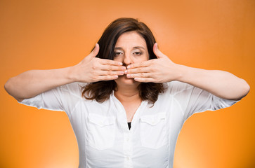 woman covering mouth on orange background. Speak no evil concept