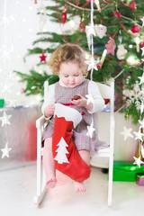 Cute smiling toddler girl checking her Christmas stocking