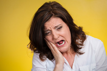 woman with sensitive tooth ache isolated on yellow background