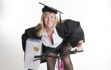 Mature student in cap gown holding present riding cycle