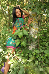 girl posing on a background of green trees