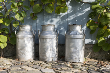 three churns on a farm