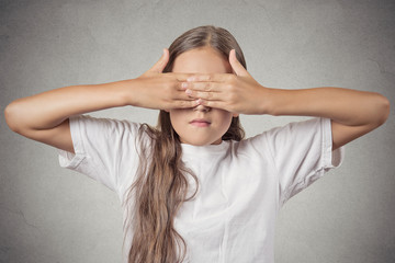 teenager girl covering eyes with hands can't see grey background