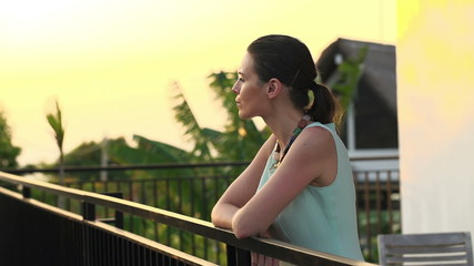 Pensive, beautiful businesswoman standing on terrace in the even