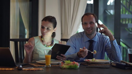 Business couple with cellphone, tablet computer and laptop eatin
