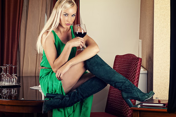 beautiful woman in a green dress with a wine glass