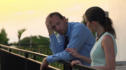 Businesswoman comforting sad, overwhelmed businessman on terrace