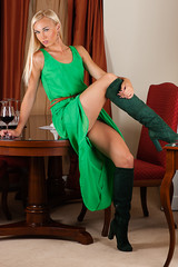 beautiful sexy woman in a green dress with a wine glass