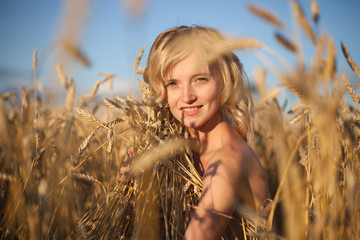 Pretty Young woman in Summer Meadow at yellow sunset