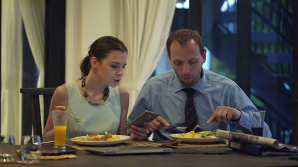 Business couple eating meal and using smartphone and tablet comp