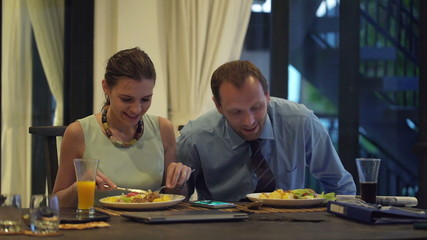 Business couple eating dinner and chatting at home in the evenin