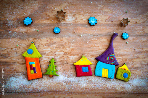 Leinwandbild Motiv Sweet village. Colorful cookies on wooden background