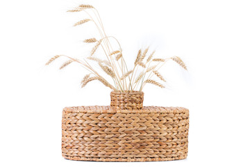 Wicker vase with wheat ears.